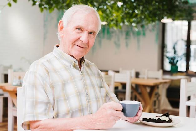 Пожилой мужчина пьет чай и смотрит в камеру