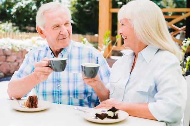 屋外のベランダでお茶を飲む年配のカップル
