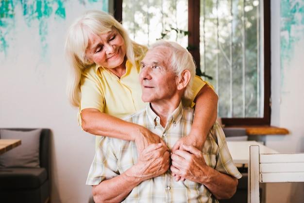 Пожилая женщина обнимает пожилого мужчину, сидящего дома