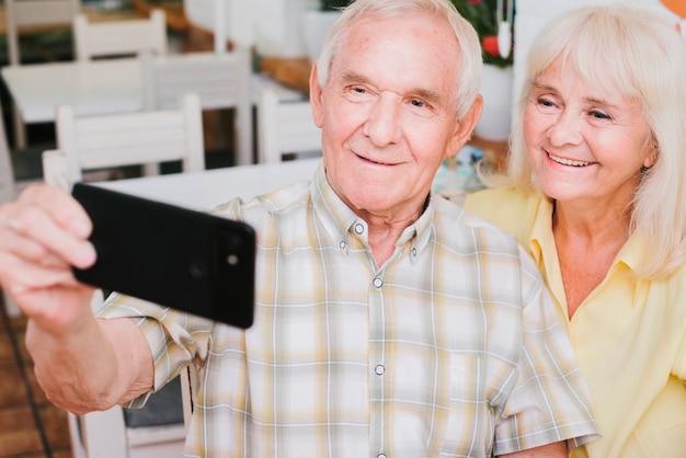 Пожилая пара принимает селфи, улыбаясь дома