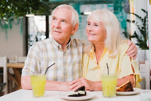 屋外テラスで食事をしている年配のカップル