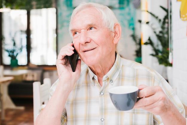 Пожилой мужчина разговаривает по телефону с чашкой в руке