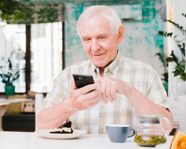 幸せな老人男性のカフェに座っていると携帯電話にテキストメッセージ