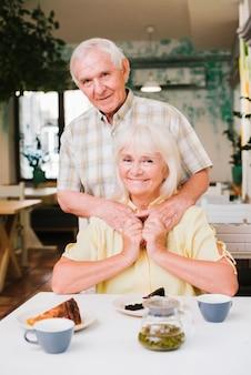 カフェに座って喜んでいる老夫婦