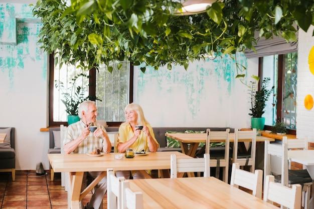 お茶のマグカップとカフェに座っている老夫婦の笑顔