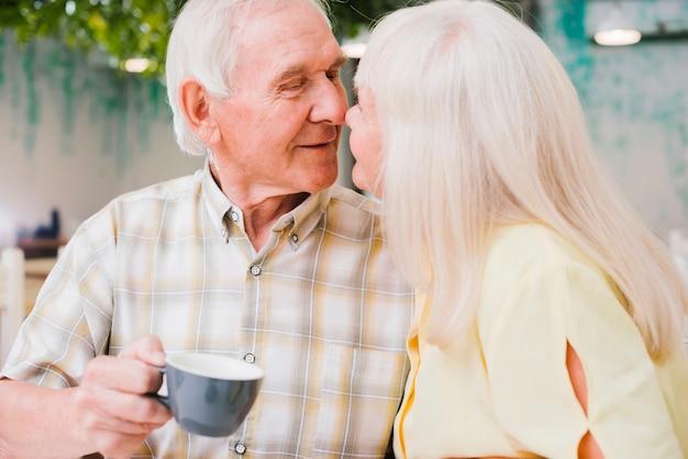 Довольная влюбленная пара с чаем в кафе