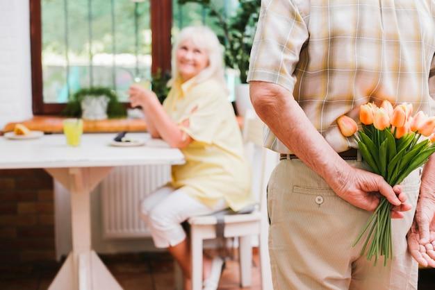 配偶者のための花束を準備する作物老人