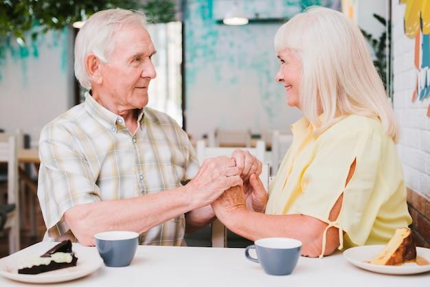 Романтическая пара старших, сидя в кафе