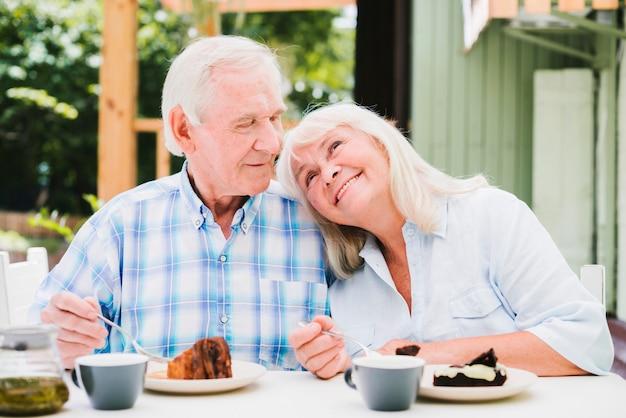 テラスでカフェに座っていると抱きしめるロマンチックな年配のカップル