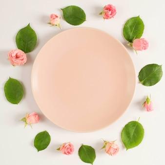 Пустая тарелка в окружении красивого розового цветка и листьев, расположенных в круговой рамке