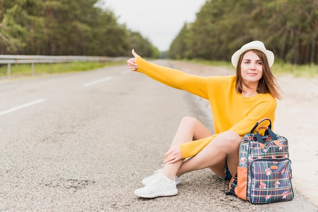 ヒッチハイクと座っている旅行の女性
