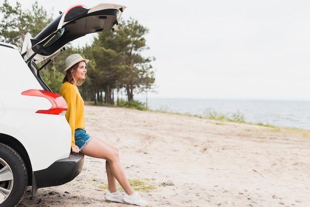 旅行の女性と彼女の車のロングショット