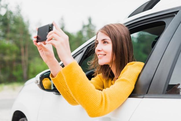 写真を撮る車の中で女性