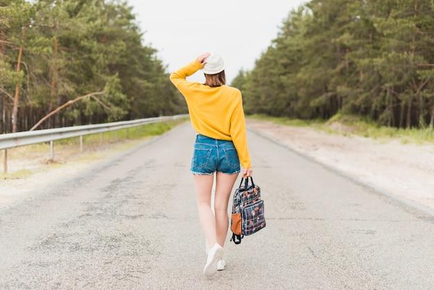 道路上の旅行の女性の背面図