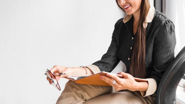 サイドビューの女性がノートをチェック