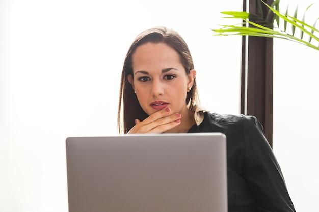 彼女のラップトップを強調して見ている正面の女性