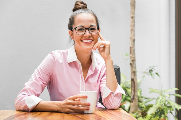 彼女の机でメガネを持つ女性実業家