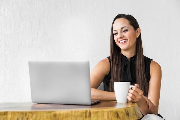 笑顔と彼女のラップトップをチェックする女性