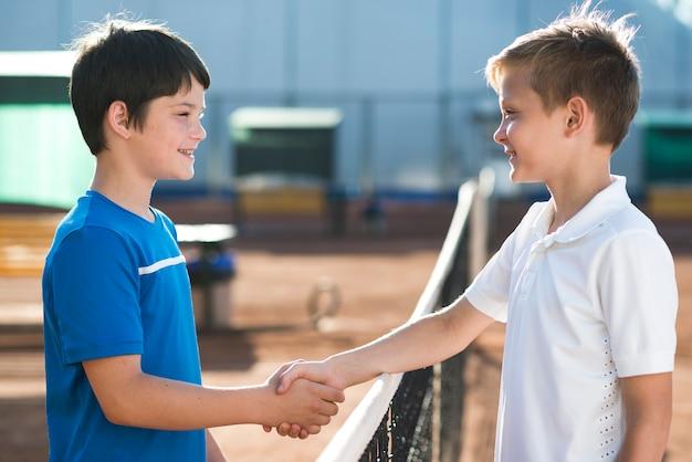 Боком дети пожимают руки перед игрой
