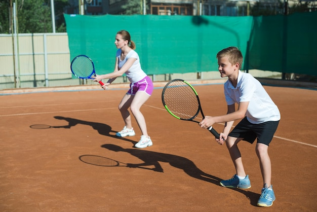 Женщина и ребенок играют в теннис