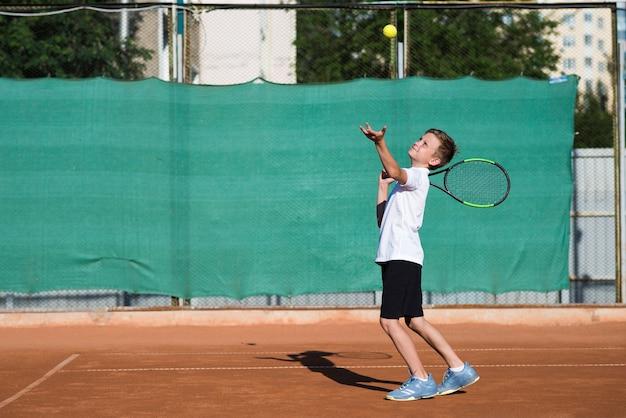 ロングショットの子供がテニス場でサービング