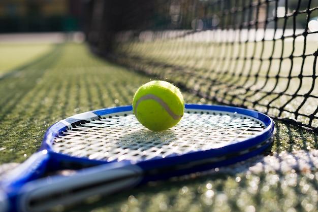 クローズアップテニスラケットとボールが地面に
