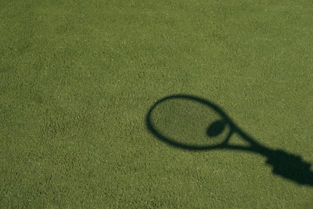 ボールとテニスラケットの影