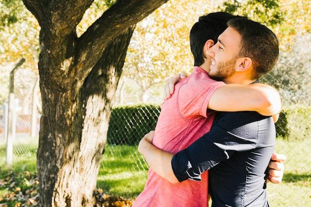 幸せな同性愛者のカップルが公園で抱きしめる