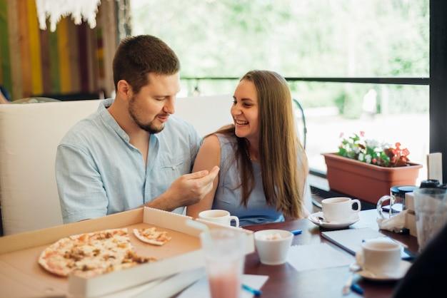 若い男と女のピッツェリアで一緒に時間を過ごす