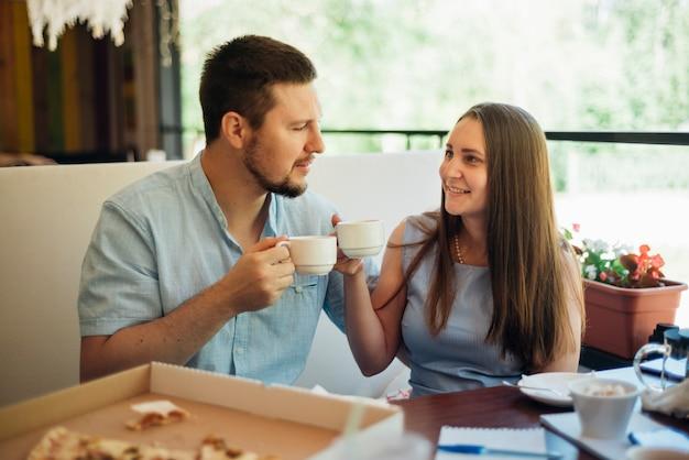 コーヒーを飲みながら朝食を食べて幸せなカップル