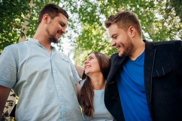 満足している人々が公園で抱いて笑って