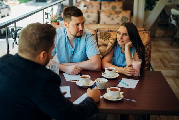 Расслабленные люди общаются и пьют кофе и молочный коктейль в кафе