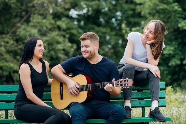 コンテンツの人々がベンチに座ってギターを弾く