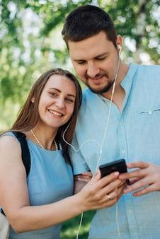 カップルが公園でスマートフォンで音楽を聴く