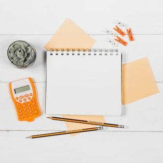 オレンジ色の消耗品に囲まれたノートブックモックアップのフラットレイアウト