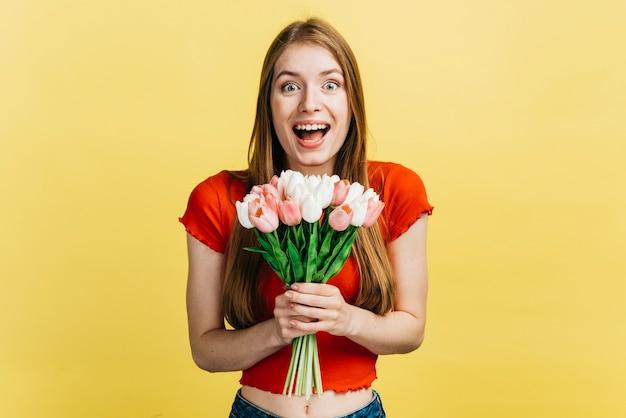 Счастливая женщина держит букет тюльпанов