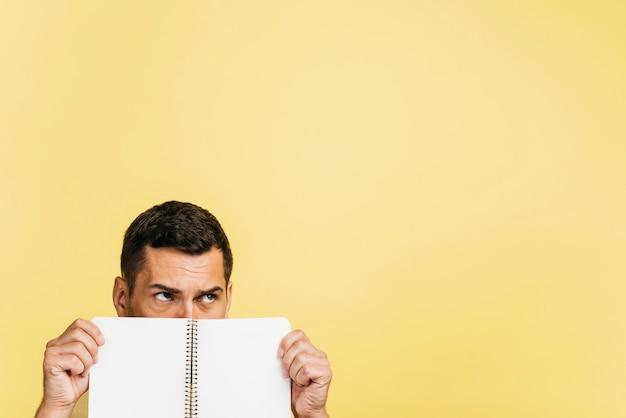 空のノートブックで顔を覆っている男