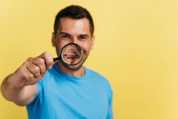 拡大鏡で口を覆っているミディアムショットの男