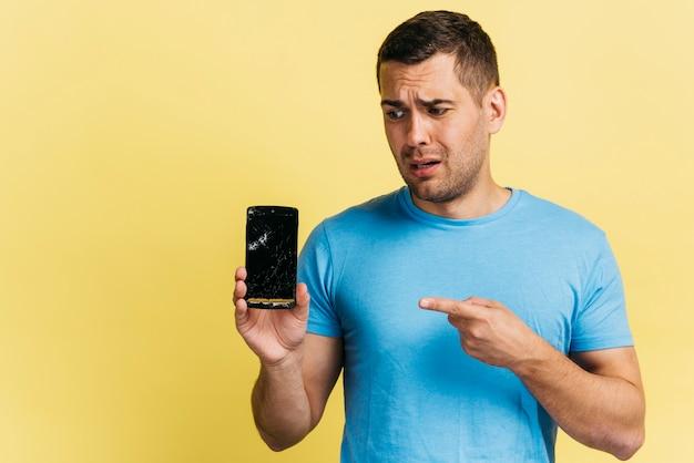 壊れた電話を保持している男