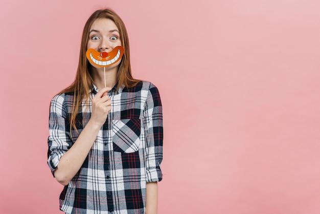 Женщина держит поддельную улыбку, прикрывая рот