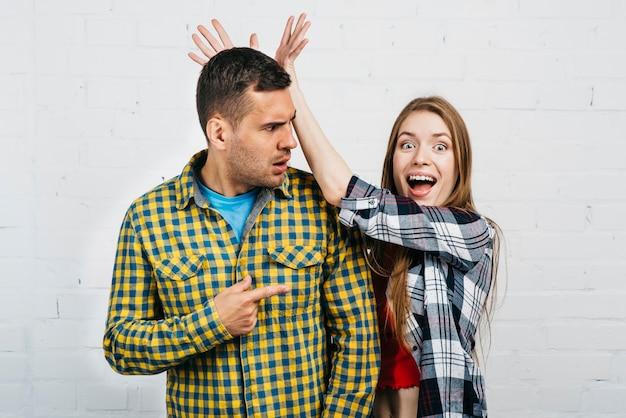 怒っている男の後ろに愚かな女性