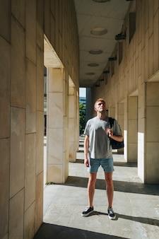 現代人のバックパックの柱の近くに立っていると見上げる