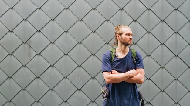 Портрет молодого мужчины путешественника с рукой пересекли стоя возле текстурированной стены