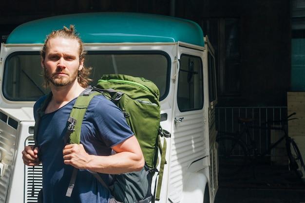 屋外でカメラを見てバックパックを運ぶ深刻な若い男
