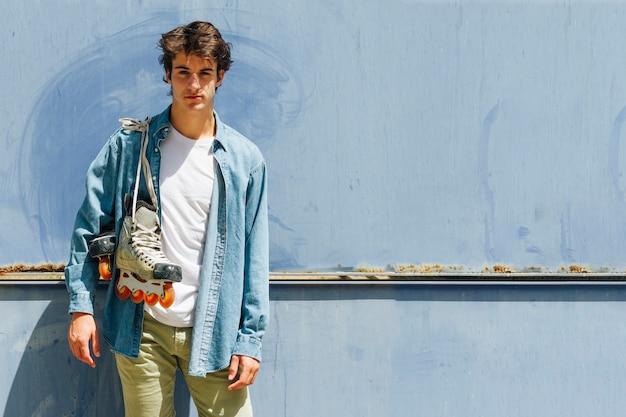 若い男がカメラを見て青い背景に立っているローラースケートを運ぶ