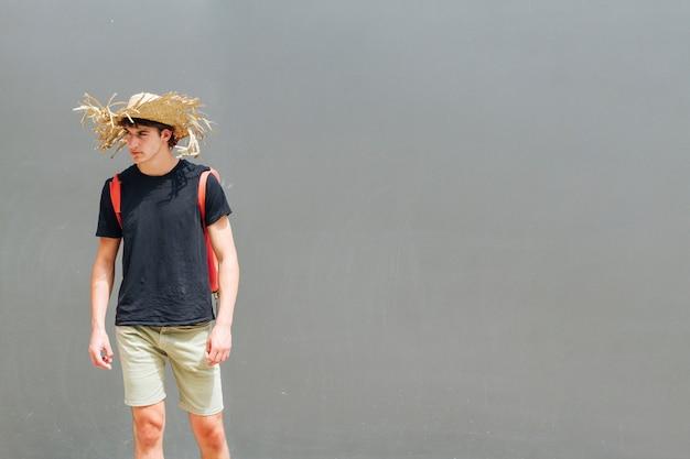 Модный молодой красавец с соломенной шляпе и рюкзак стоял на сером фоне