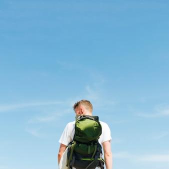 青い空を背景に立っている若い男の後姿
