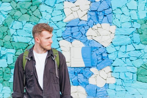 離れている塗られた石の壁の近くに立っている若い男のクローズアップ