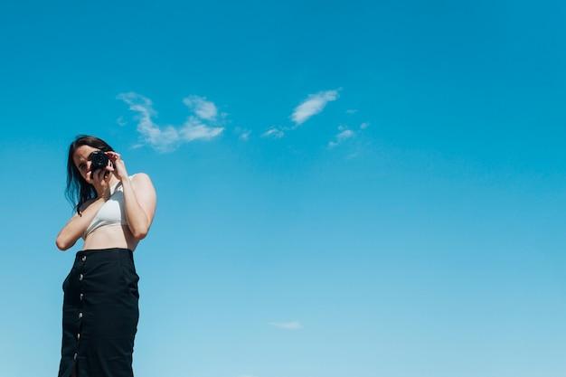 スタイリッシュな女性写真家、青い空を背景にカメラで写真を撮る