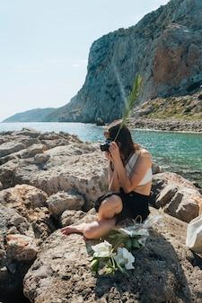 カメラで写真を撮っている間ヤシの葉を保持している岩の上に座っているスタイリッシュな女性